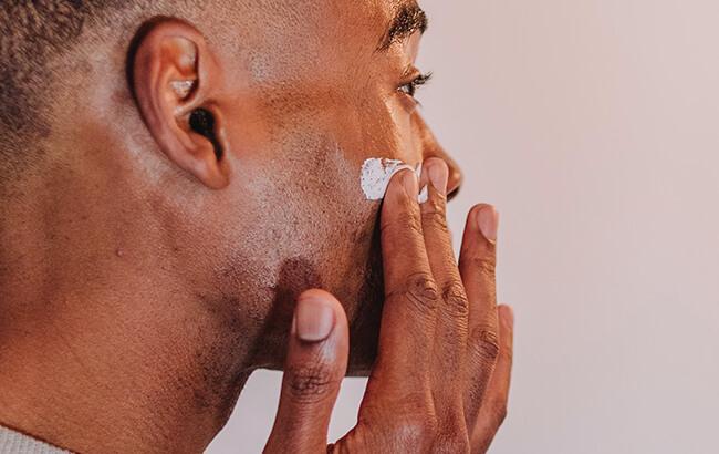 man applying skincare on face